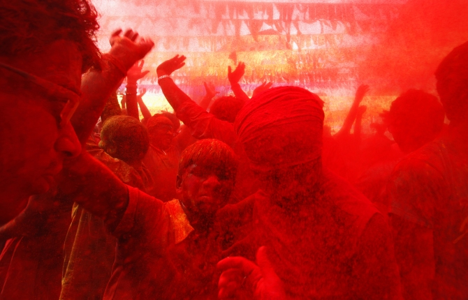 A girl sits on her father's shoulders cheers as she and others daubed in colours dance while celebrating Holi in Guwahati.
