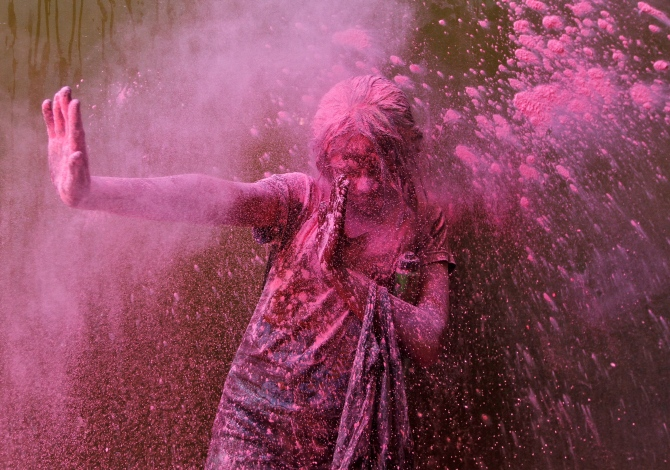 A girl smeared with colours reacts as another girl throws coloured powder at her during Holi celebrations in Chennai.