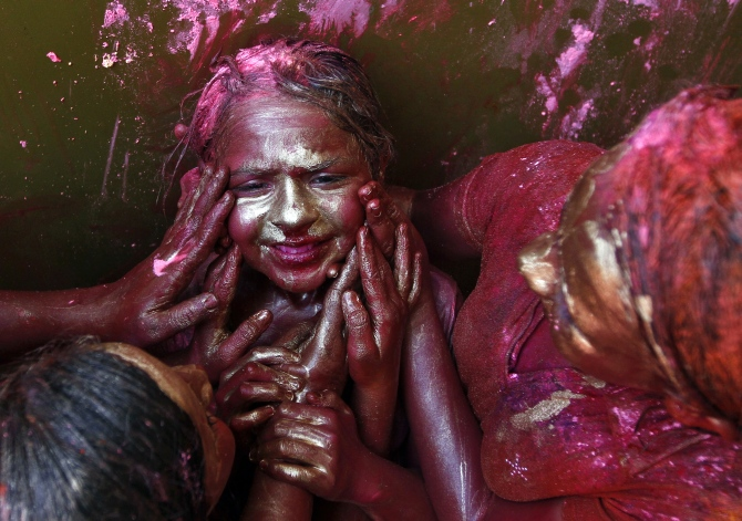A girl reacts as other girls apply coloured paint on her face during Holi celebrations in  Chennai.