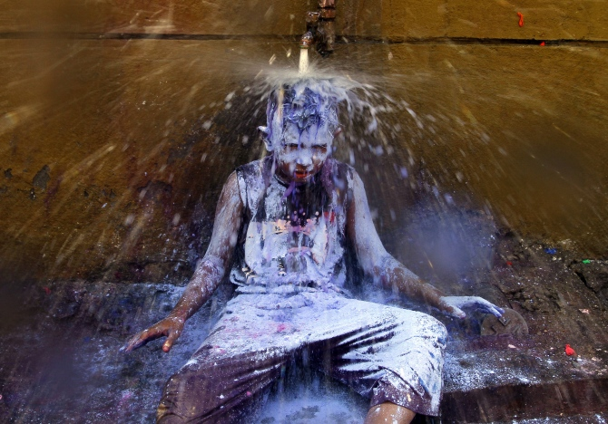 A boy sits under a water tap to wash himself after taking part in Holi celebrations in Chennai.