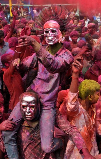 People painted with bright colors dance during Holi in Fancy Bazar, the main commercial centre in Guwahati, on Monday.