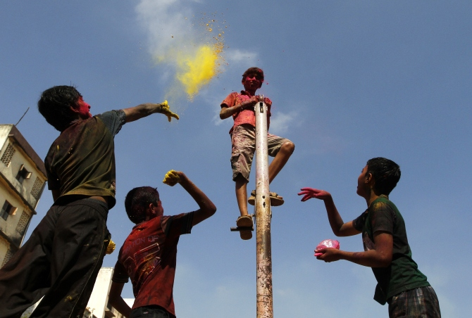 Boys throw coloured powder at another boy standing on a pole as they take part in Holi celebrations in Chennai.