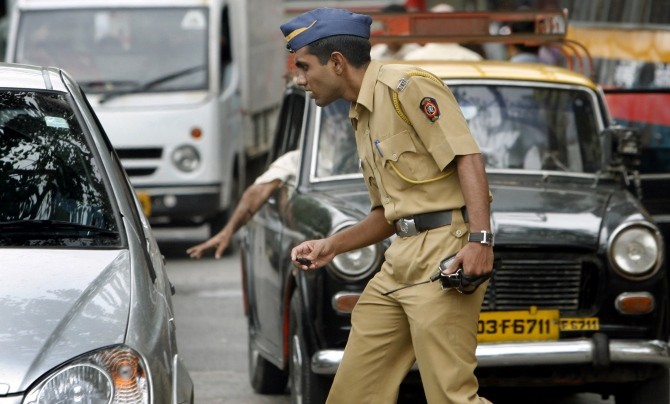 A policeman controls traffic on a busy road in Mumbai