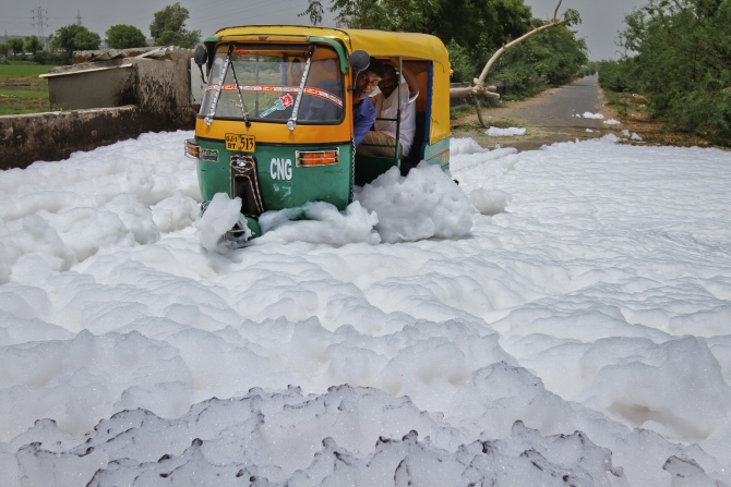 A man looks out of his auto rickshaw as he drives through foam overflowing from a drain outside a factory, in Ahmedabad.