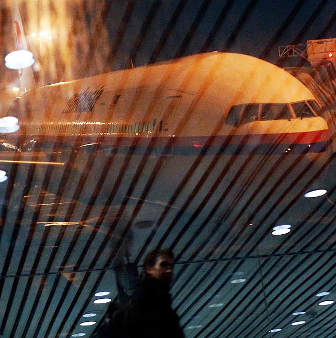 A Malaysia Airlines Boeing 777-200ER, flight 318 to Beijing, sat on the tarmac Monday at Kuala Lumpur International Airport. Flight 318 replaces 370, retired out of respect to the passengers and crew of the missing plane