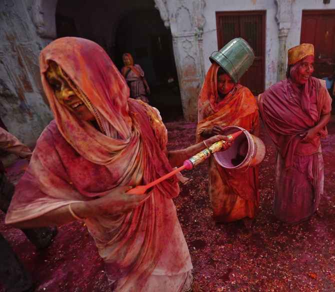 Widows daubed in colours as they take part in Holi celebrations organised by non-governmental organisation Sulabh International at a widows' ashram in Vrindavan