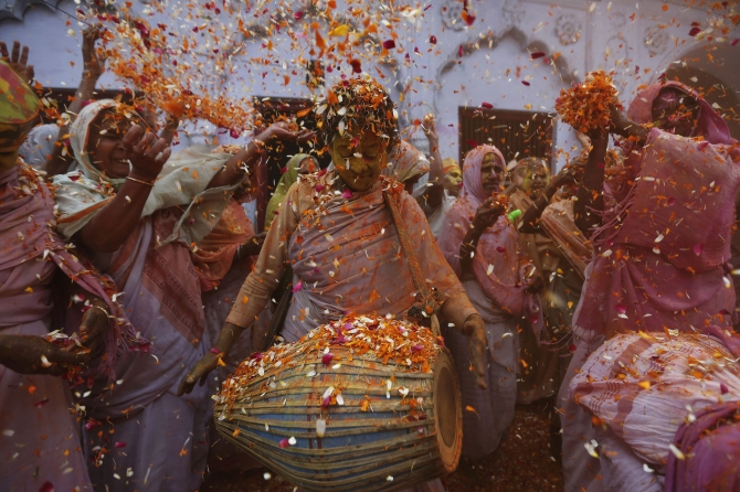 A widow plays 'dholak' during Holi celebrations at the ashram