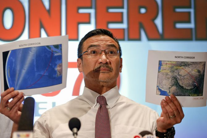 Malaysia's acting Transport Minister Hishammuddin Hussein shows two maps with corridors of the last known possible location of the missing Malaysia Airlines MH370 plane as he addresses reporters at the Kuala Lumpur International Airport