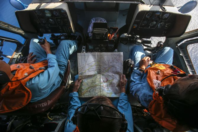 Military personnel work within the cockpit of a helicopter belonging to the Vietnamese airforce during a search and rescue mission off Vietnam's Tho Chu island