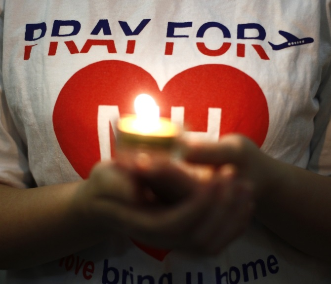 A woman holds a candle during a special prayer for passengers onboard the missing Malaysia Airlines Flight MH370 at the Chinese Assembly Hall in Kuala Lumpur