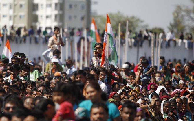 A Congress supporter takes a picture while listening to Rahul Gandhi during a rally in Bardoli, Gujarat