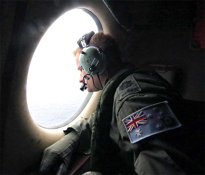 Royal Australian Air Force Warrant Officer Michal Mikeska looks out of a RAAF C-130J Hercules aircraft as it flies over the southern Indian Ocean during the search for the missing Malaysian Airlines flight MH370