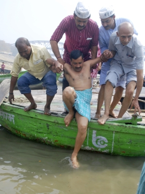 Arvind Kejriwal, helped by supporters, prepares to take a dip in the waters of the Ganga in Varanasi.