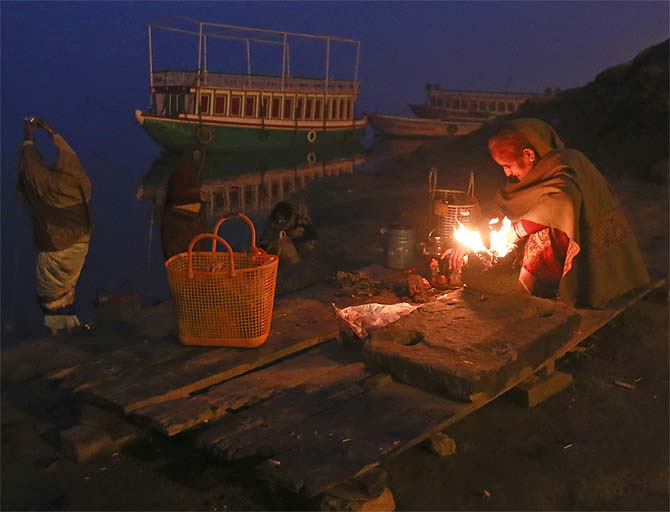 A devotee warms herself around a fire as others pray at dawn on the banks of Ganga in Varanasi