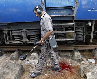 A member of the bomb disposal squad examines the area next to the Bangalore-Guwahati Kaziranga Express on which the explosions occurred.