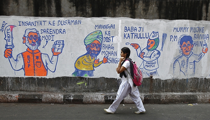 A school girl walks past a wall with graffiti depicting Indian politics ahead of the general election.