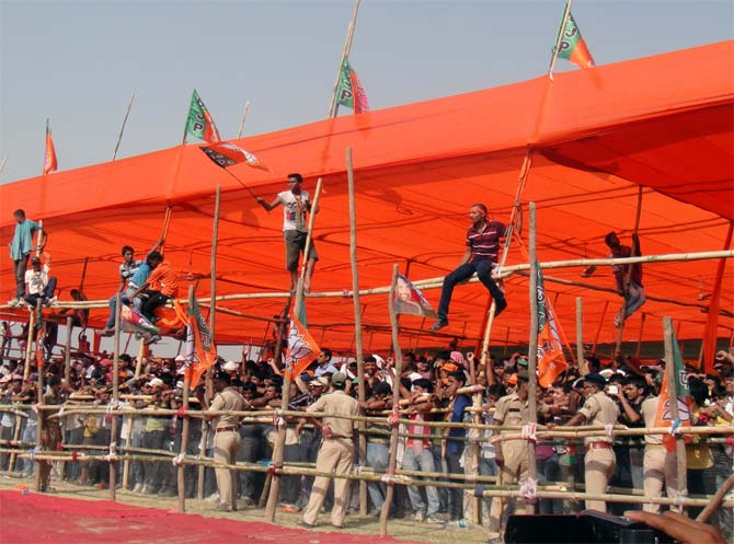 Enthusiastic supporters climb bamboo scaffolding to get a better view of Modi at the Chhapra rally.