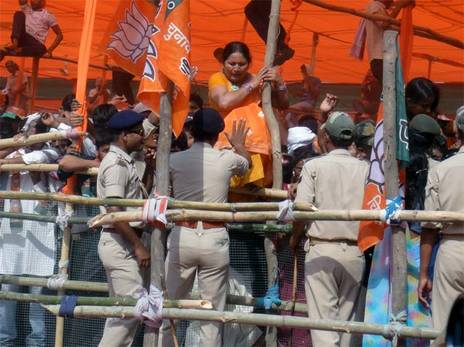 Women climb out of the enclosure to avoid being crushed by the men at the Modi rally in Chhapra, Bihar.