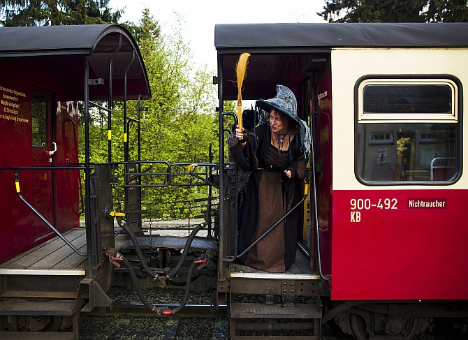 A woman holds a broom as she travels on the HSB light railway through the Harz mountains to celebrate the Walpurgisnacht pagan festival