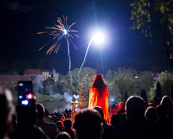 A man dressed as devil towers over revellers as they watch fireworks explode over a Walpurgisnacht pagan festival in the town of Stiege, in the Harz mountain region