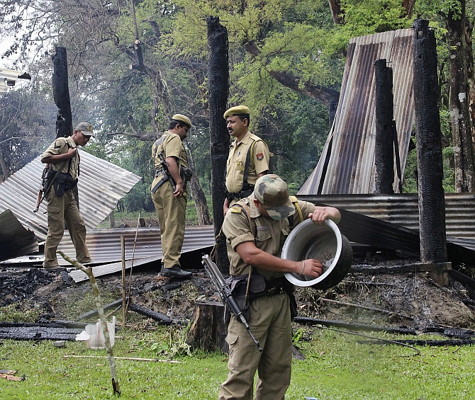 Security personnel inspect the debris of the houses that were burnt during attacks at Baksa district of Assam
