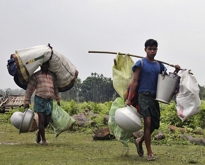 Villagers carry their belongings as they leave their locality after attacks at Baksa district