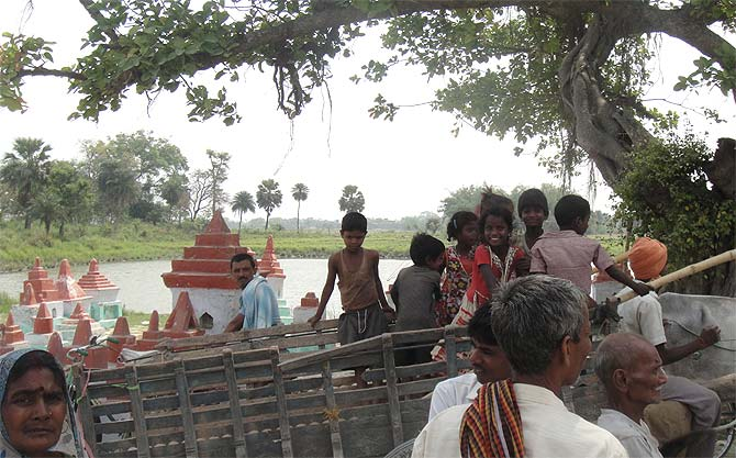 Children on a bullock cart pass by the school area in Gandaman.