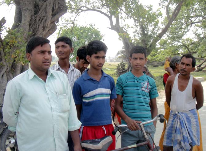 Villagers outside the school area in Gandaman.
