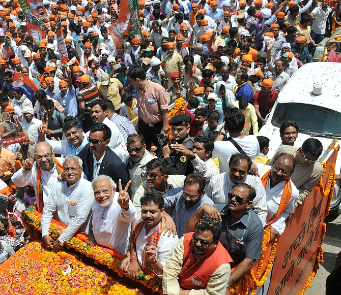 Narendra Modi and Amit Shah show the victory sing during a roadshow in Varanasi
