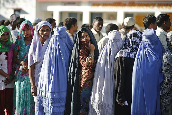 Voters queue at a polling station to cast their votes in Shabazpur Dor village, in Amroha district in UP