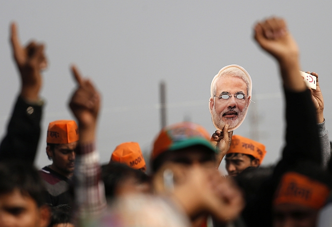 A supporter of Modi holds out a mask during a rally in Meerut