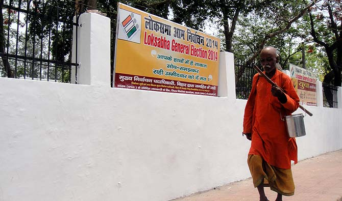 A man in saffron robes walks past a poll banner at the Saran Collectorate. Photograph: Archana Masih/Rediff.com