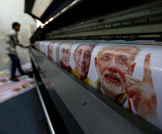 A worker prints banners of Narendra Modi and other BJP leaders.