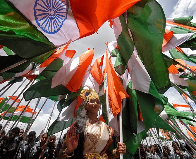 A woman dressed as Mother India poses with national flags
