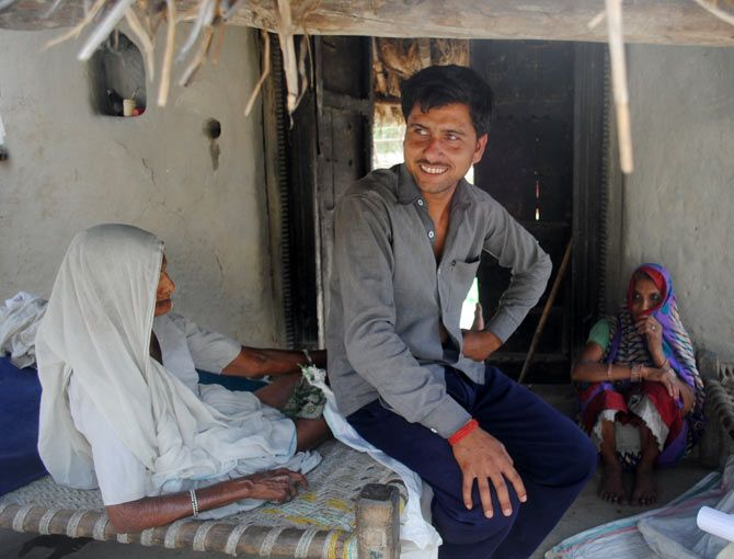 Sonu Singh, a farmer, sits inside his kucchha house. He says he does not have enough money to repair his thatched roof before the rains.