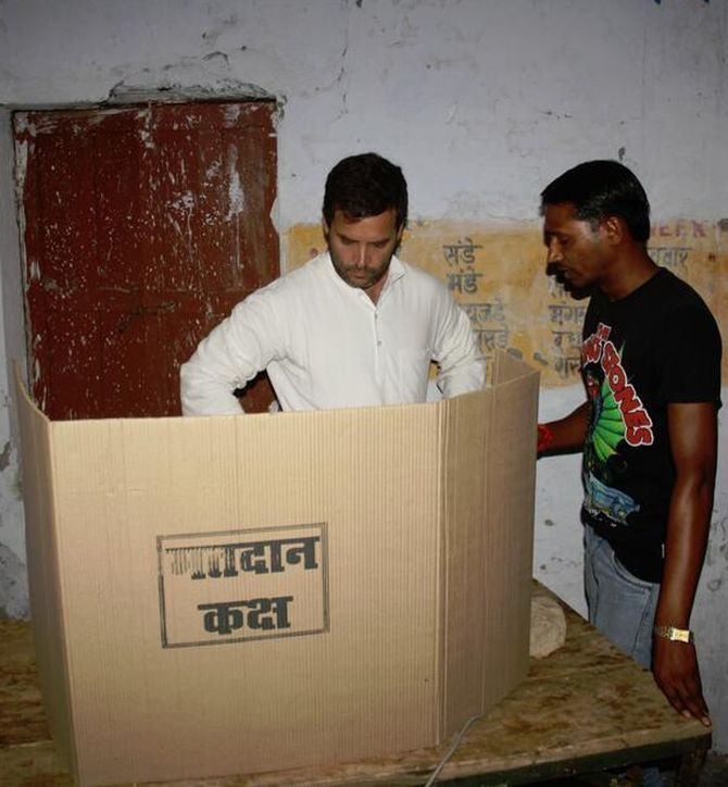 Rahul Gandhi at a poll booth in Amethi with a voter.