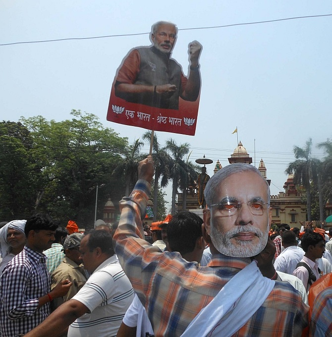 A BJP supporter wearing a Modi mask joins the protest outside BHU