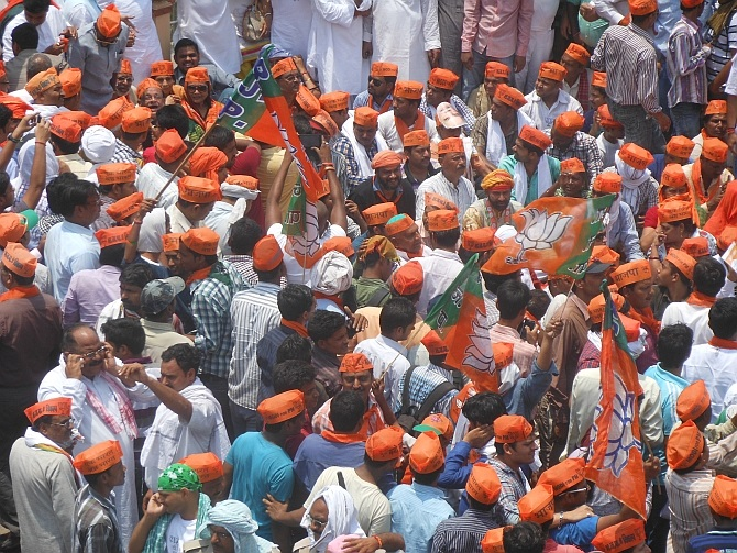 Supporters wave BJP flags as the join the stir