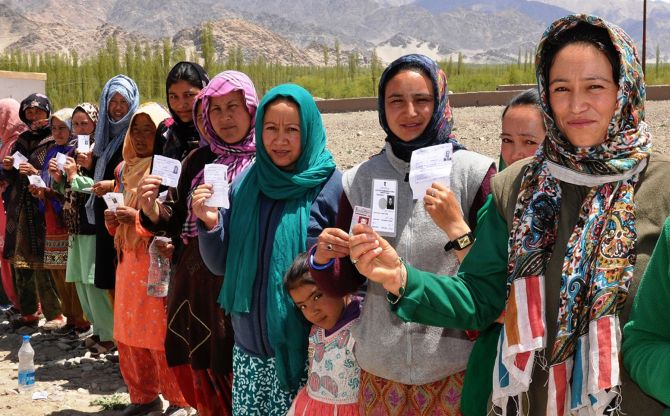 Ladakhi women show their voter cards as they wait in line outside a polling booth