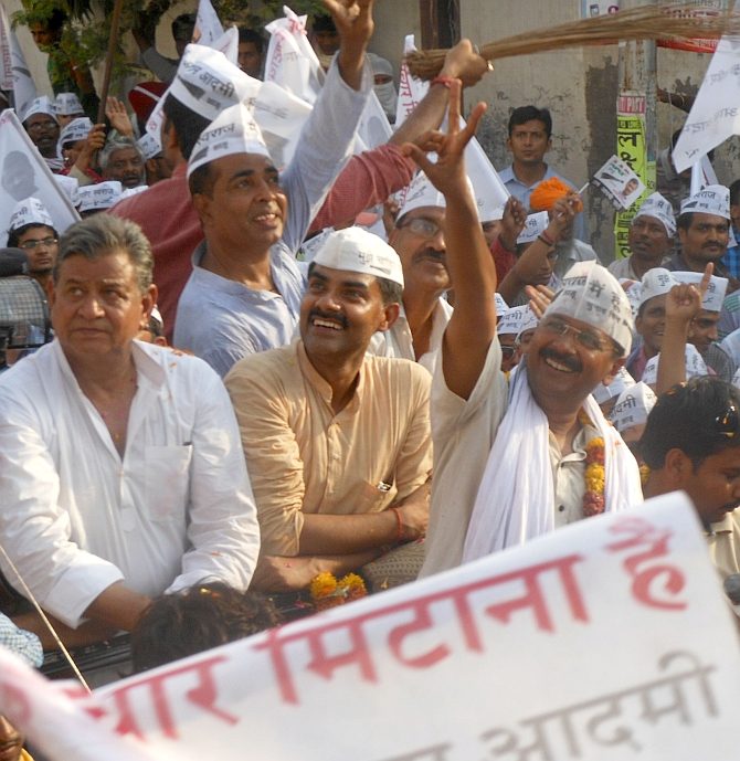 Arvind Kejriwal shows the victory sign to supporters during a roadshow in Varanasi