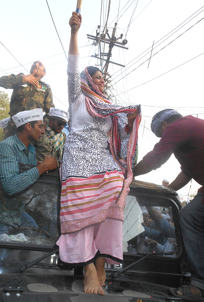 AAP's Shazia Ilmi waves the broom, the party symbol, as she stands atop the jeep