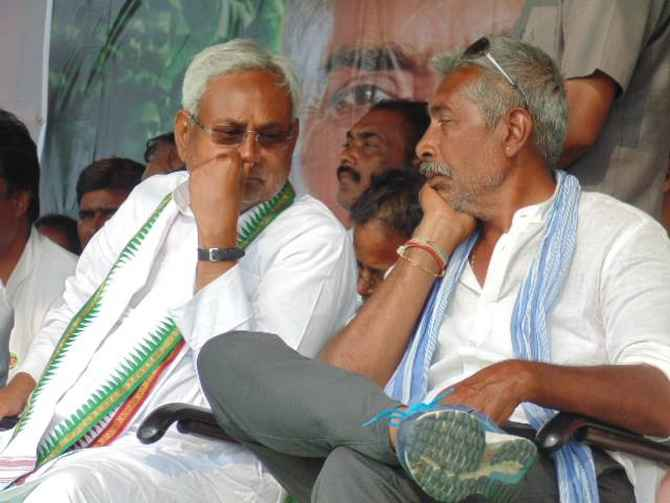 Bihar Chief Minister Nitish Kumar speaks to Prakash Jha during a rally in West Champaran district