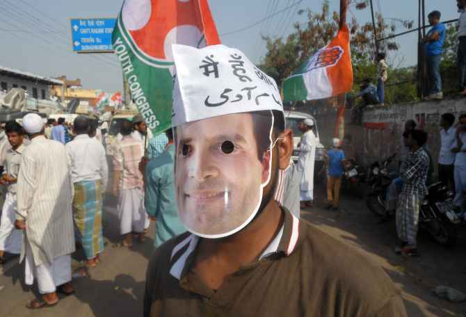 A Congress supporter wears a Rahul Gandhi masks during the roadshow on Saturday