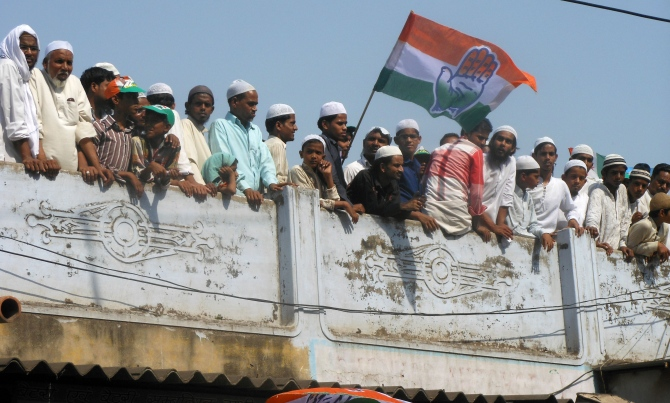 Curious Muslim youth gather on rooftops to take a look at the rally.
