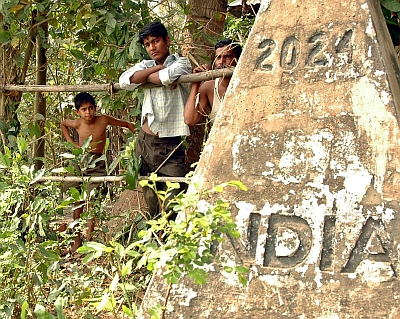 Bangladeshi residents watch as Indian officials prepare to build a fence on the border in Tripura in 2006