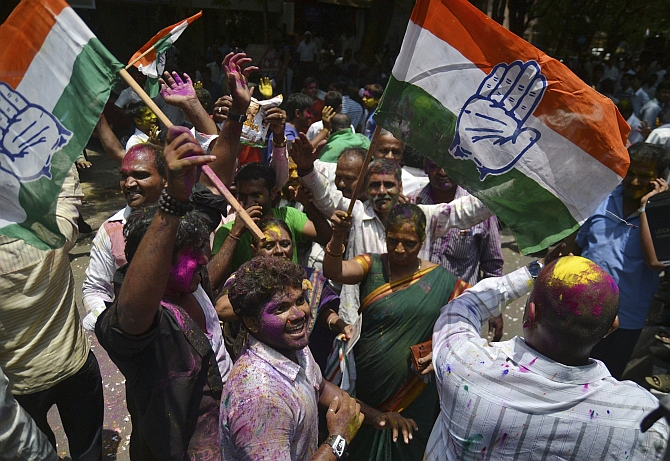 Supporters of the Congress celebrate as they hold their party flags outside a vote counting centre in Bangalore