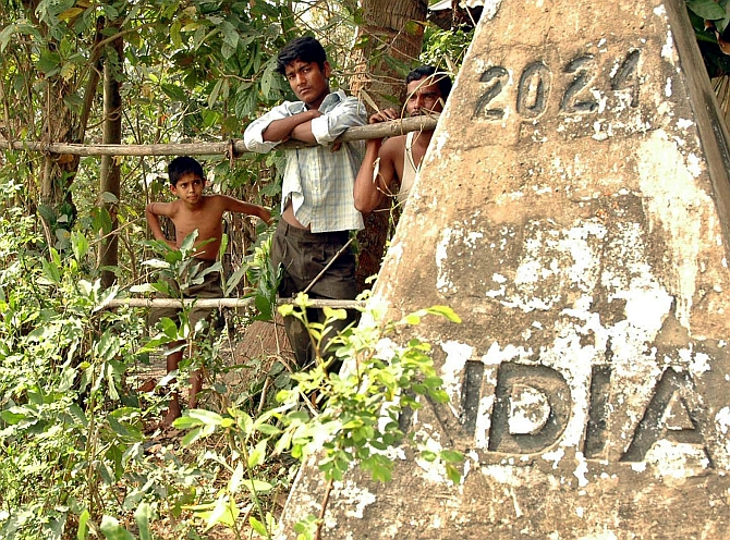 Bangladeshis watch Indian officials (not in the frame) take measurements for a border fence at the zero point that divides India and Bangladesh in Agartala