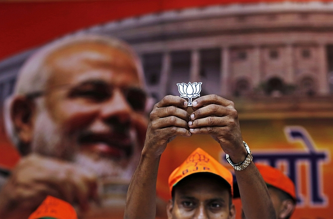 A BJP supporter shows the party symbole, the lotus, in New Delhi