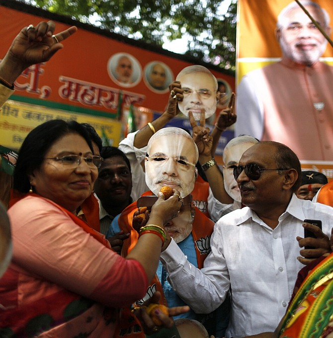 Supporters of the Bharatiya Janata Party hold up a mask of Narendra Modi in Mumbai