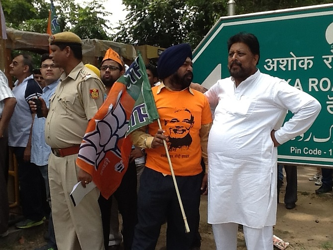 A BJP supoorter sporing a Modi tee-shirt and carrying the party flag at the roadshow